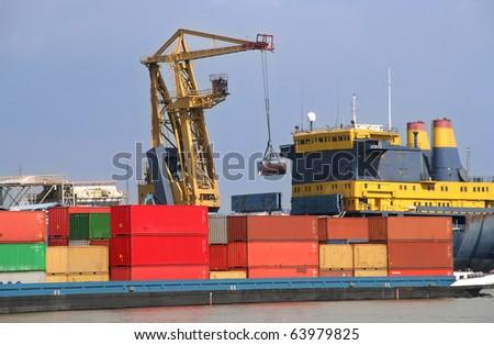 Harbor crane loading a container ship - stock photo