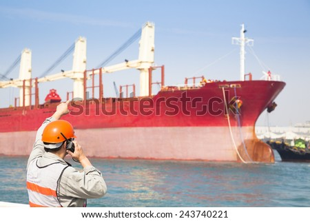 Harbor dock worker talking on  radio with ship background - stock photo