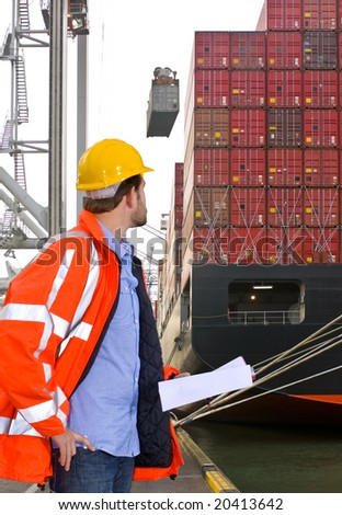 Harbor employee overseeing the loading of a huge container ship