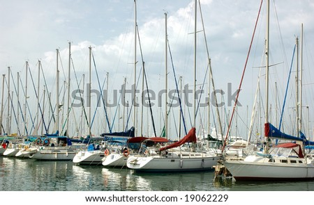 Harbor full of yachts and Flagpoles - stock photo