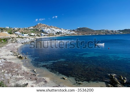 Harbor of Mykonos showing the crystal clear waters and the white washed buildings - stock photo