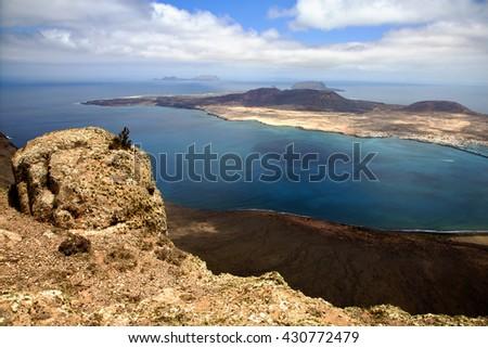 harbor rock stone sky cloud beach  water  coastline and summer in lanzarote spain graciosa miramar del rio - stock photo