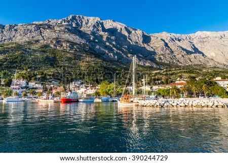 Harbor With City And Biokovo Mountain In The Background  - Baska Voda, Makarska, Dalmatia, Croatia - stock photo