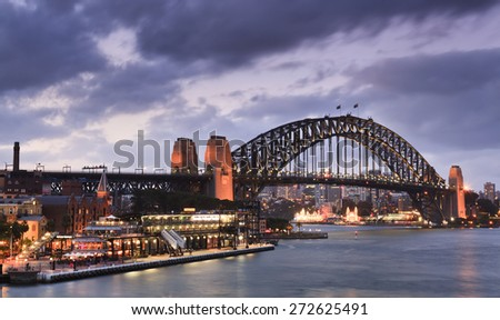 Harbour bridge in Sydney - side view from Circular Quay at sunset under heavy clouds highly illuminated - stock photo