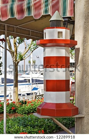 Harbour Town, Hilton Head Island in South Carolina.  Strip of shops along the harbor. Replica of larger lighthouse in the harbor. - stock photo