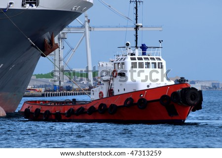 Harbour tugboat at work. - stock photo