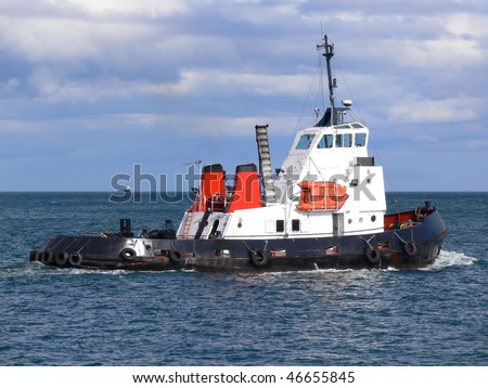 Harbour tugboat underway at sea. - stock photo