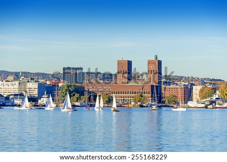 Harbour with boats and wooden yacht with town hall on background at sunset in Oslo, Norway - stock photo