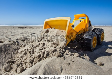 Hard at Work - under construction. Toy Front Loader Pushes Sand on the Beach at the Oregon Coast. - stock photo