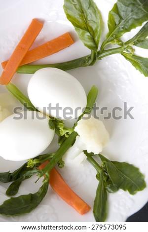 hard boiled egg and veggie on white plate - stock photo