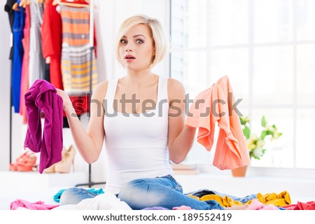 Hard choice. Beautiful young blond hair woman sitting on the bed and trying to choose clothes to dress  - stock photo