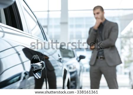 Hard choice. Selective focus on a car, man choosing car on the background - stock photo