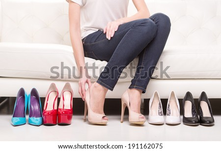 Hard choice. Woman deciding what shoes to choose. - stock photo