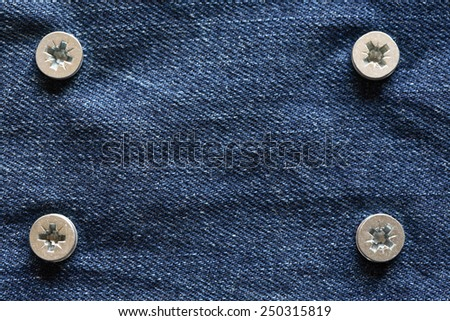Hard concept. Closeup of blue denim attached with metal screws. Nice background - stock photo