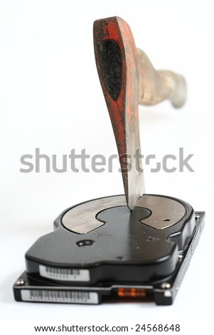 Hard disk destroyed with a dirty old axe. Useful to illustrate concepts like data  loss or data theft. - stock photo