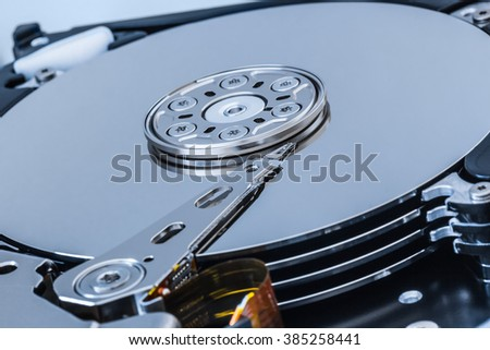 Hard disk drive open inside cylinder plates look head silver macro close up