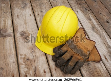 Hard hat and work gloves on wooden boards after rainfall. - stock photo