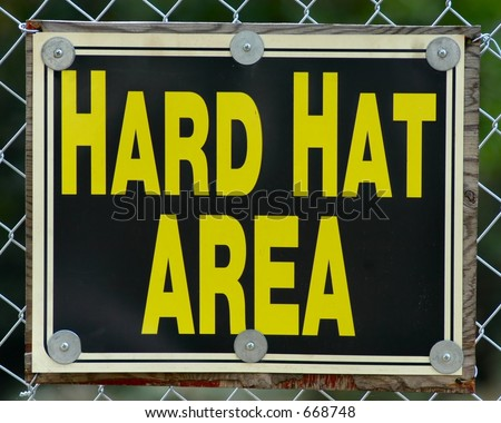 Hard hat area sign hanging on a chained link fence