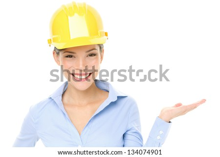 Hard hat engineer or architect woman showing pointing at copy space. Young female mixed race Caucasian / Asian Chinese professional wearing yellow hard hat isolated on white background in studio. - stock photo
