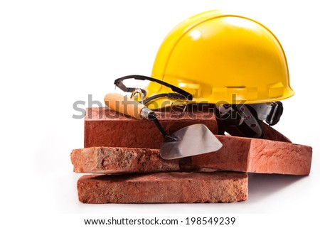 Hard hat, goggles, trowel, red brick building on a white background - stock photo