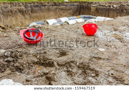 Hard hat on the construction site pipeline on the background - stock photo
