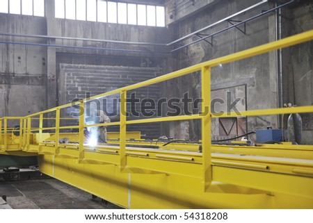 hard iron and steel industry worker working indoor in factory with weld machine - stock photo