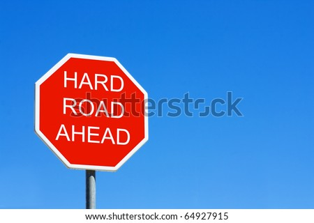 Hard Road Ahead road sign against a clear blue sky - stock photo