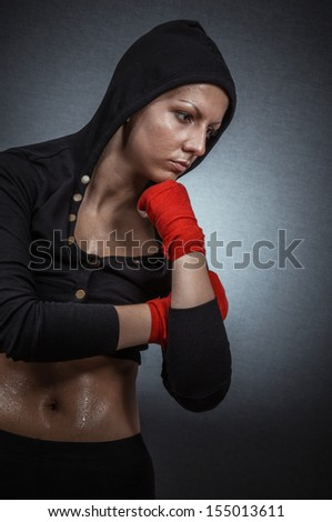 Hard sport woman ready for fight. Fighter girl with hoodie over dark gray background - stock photo