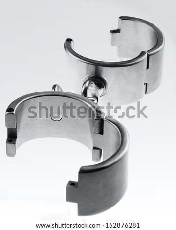 hard steel or iron handcuffs or cuffs to tie up your slave in bondage - stock photo