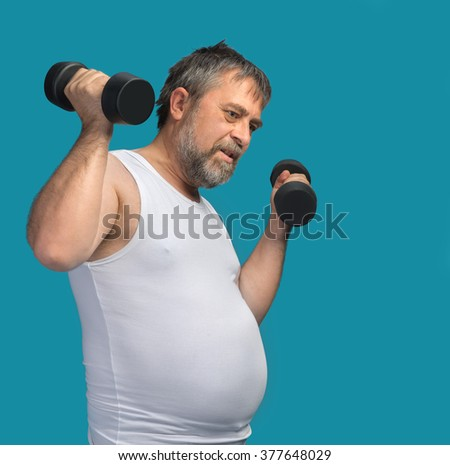 Hard work for a healthy lifestyle concept. Fat middle-aged man with a big belly does physical exercises with dumbbells - stock photo