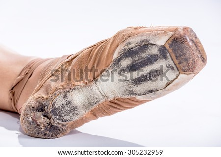 Hard worked toe dancing ballerina on white background