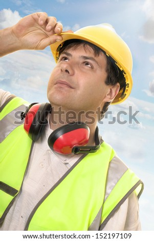 Hard working builder, construction worker or foreman looking up or overseeing progress.  Sunlit sky and clouds background  - stock photo