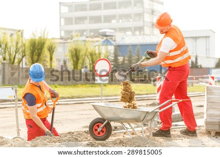 Hard working builders pouring soil in barrow - stock photo
