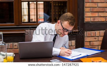 Hard working businessman in restaurant. Close-up. - stock photo