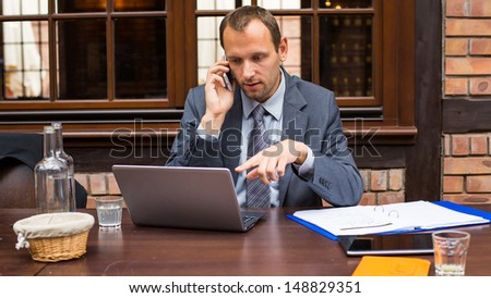 Hard working businessman in restaurant with laptop and mobile phone.