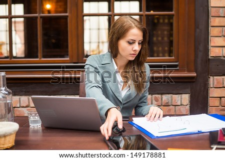 Hard working businesswoman in restaurant with laptop. - stock photo