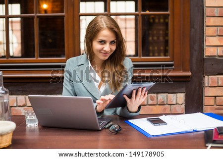 Hard working businesswoman in restaurant with laptop and pad.