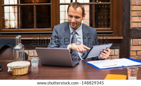 Hard working smiling businessman in restaurant with laptop and pad. - stock photo