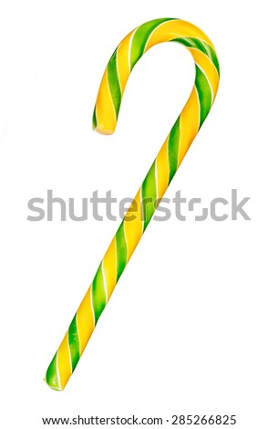 Hard yellow and green striped candy cane isolated over white background - stock photo