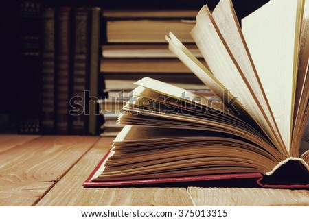 Hardback open old book with fanned pages on wooden grunge shelf table background. Instagram vintage toned photo. Books stacking. Back to school. Copy Space. Education background. - stock photo