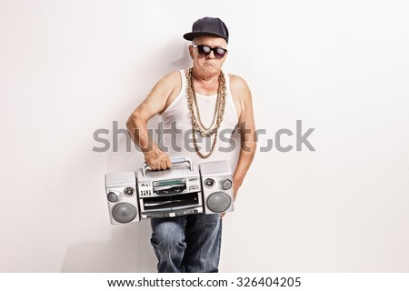 Hardcore senior rapper holding a ghetto blaster and looking at the camera - stock photo