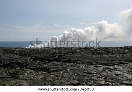 Hardened lava fields of the Kilauea Volcano with steam billowing from hot lava entering the Pacific Ocean.  Exploring the lava is a popular tourist activity on the Big Island of Hawaii. - stock photo