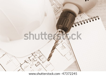 Hardhat, drill and note pad in brown tone