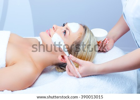 Hardware cosmetology. Closeup picture of lovely young woman with cream mask in a beauty parlour. - stock photo