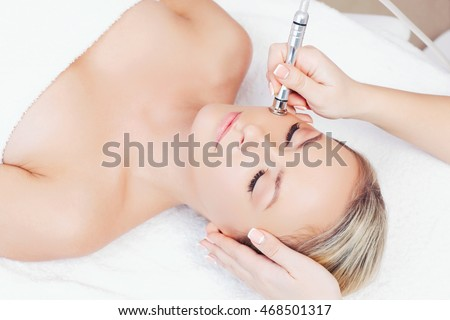 Hardware cosmetology. Closeup portrait of female face with closed eyes getting microdermabrasion procedure in a beauty parlour.