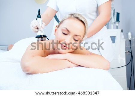Hardware cosmetology. Picture of happy young woman with closed eyes getting rf lifting procedure in a beauty parlour.