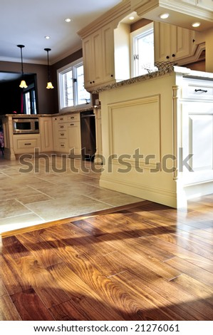 Hardwood and tile floor in residential home kitchen and dining room - stock photo
