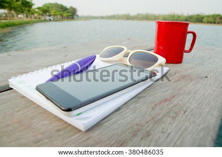 hardwood desk with laptop, tablet, smartphone,notebook,sunglass and a cup of coffee - stock photo