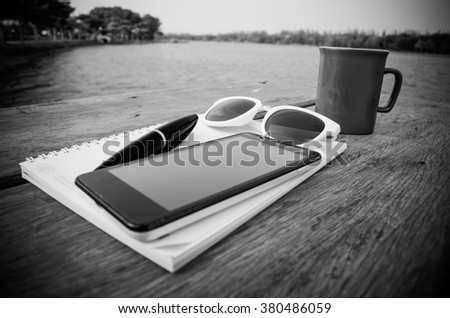 hardwood desk with laptop, tablet, smartphone,notebook,sunglass and a cup of coffee,black white color - stock photo