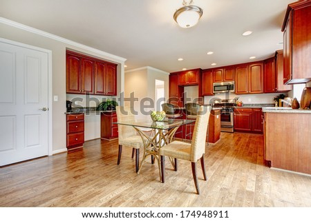 Hardwood floor big kitchen room with cherry wood cabinets and light tones dining table set - stock photo